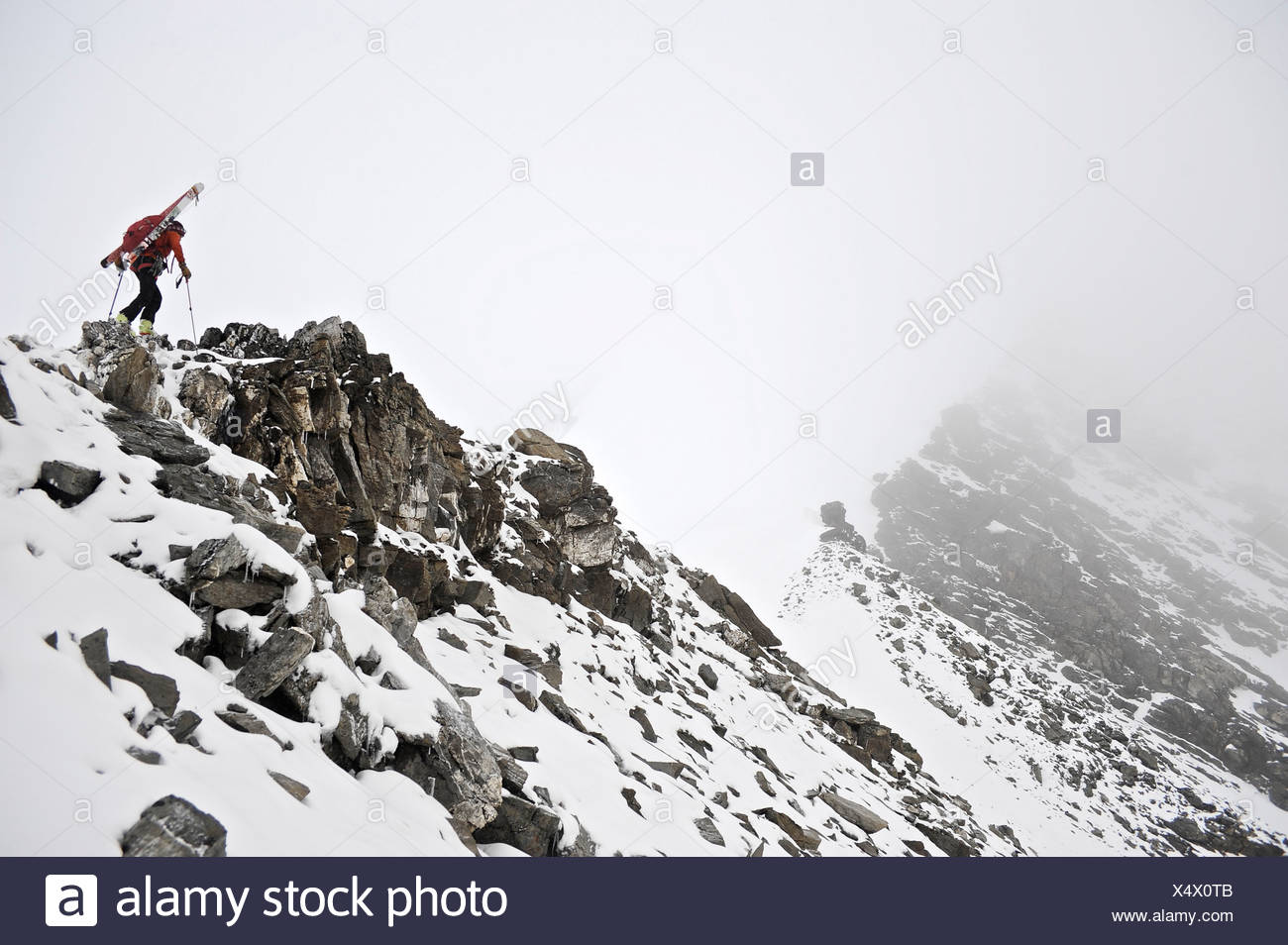 Backpacker climbs the West Ridge of Mt. Chamberlin in the Brooks Range, ANWR, Arctic Alaska, Summer - Stock Image