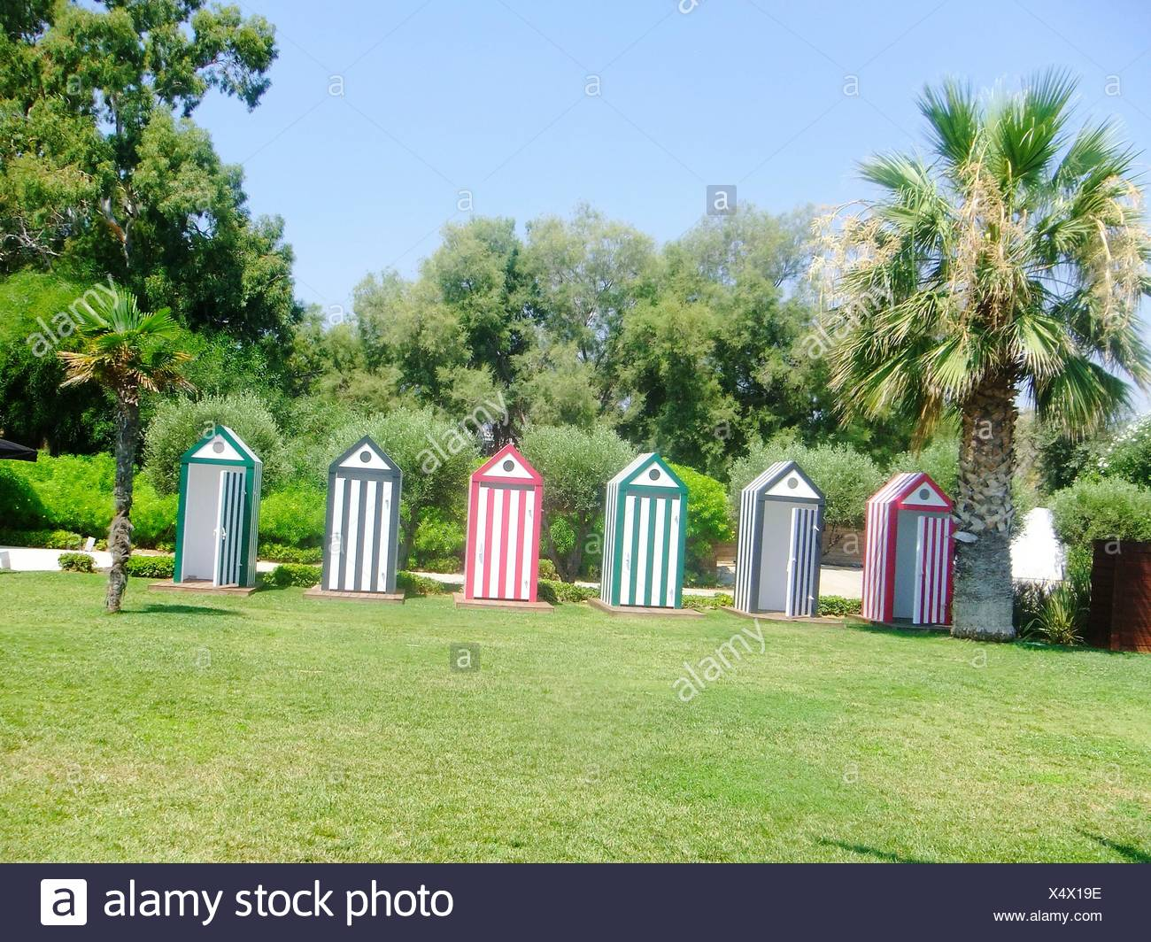 Public Restrooms On Grassy Field Against Clear Sky - Stock Image