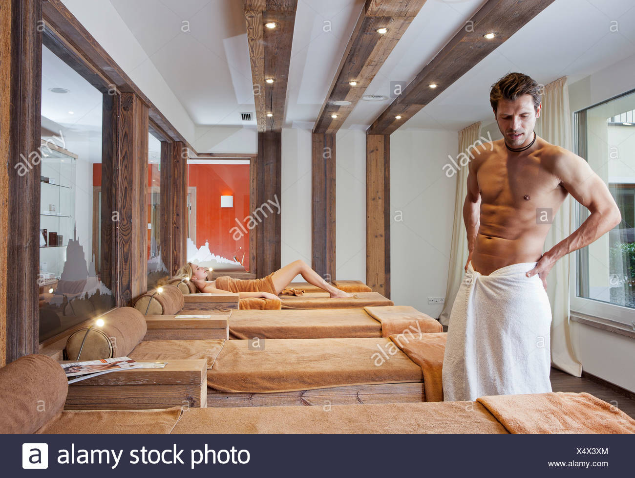 Man and woman relaxing in the relaxation area of a sauna - Stock Image