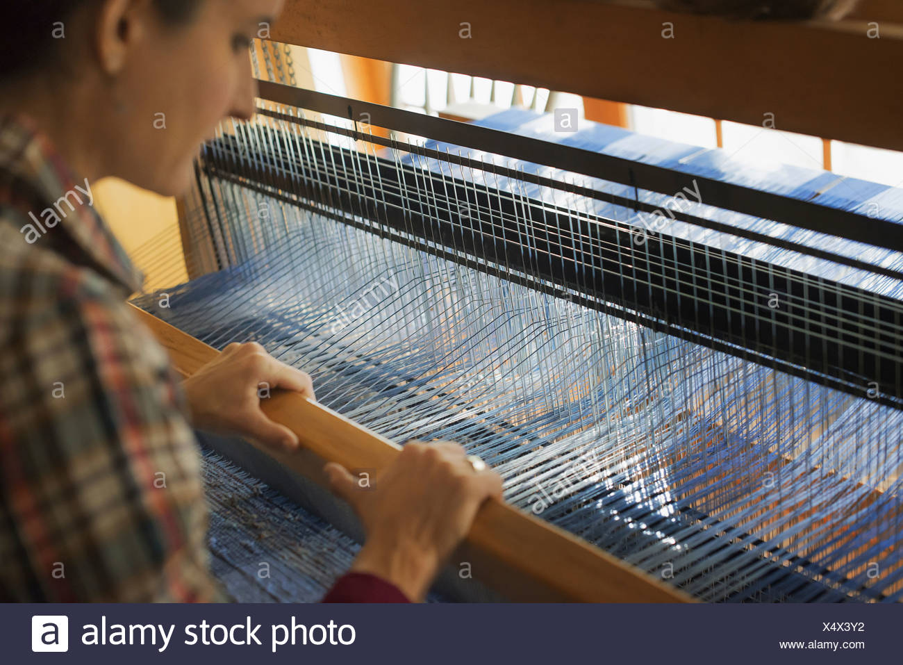 A woman seated at a wooden handloom creating a hand-woven woollen fabric with a blue and white pattern - Stock Image