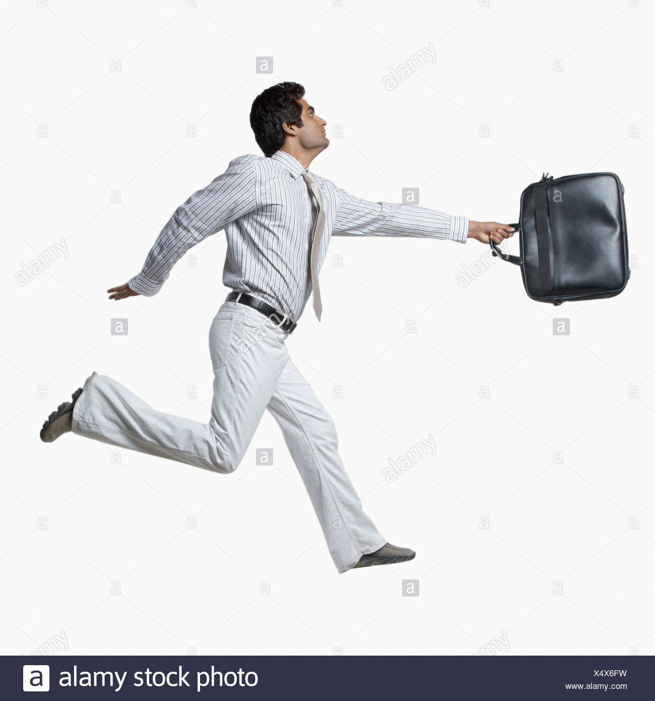 Side profile of a businessman carrying a hand bag and running - Stock Image