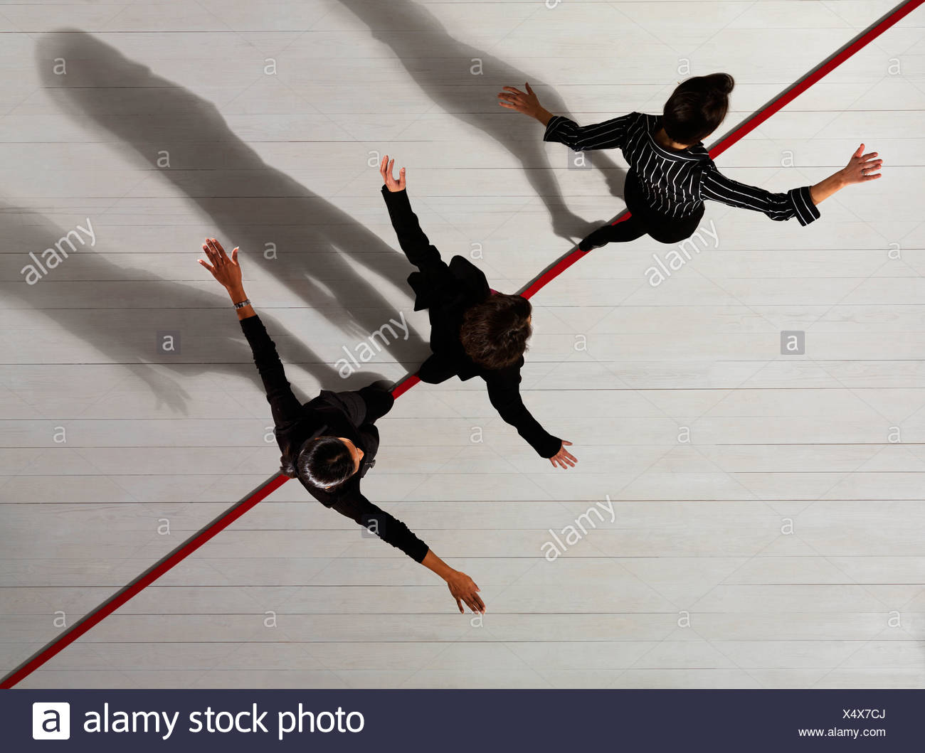 Business women walking along red line - Stock Image