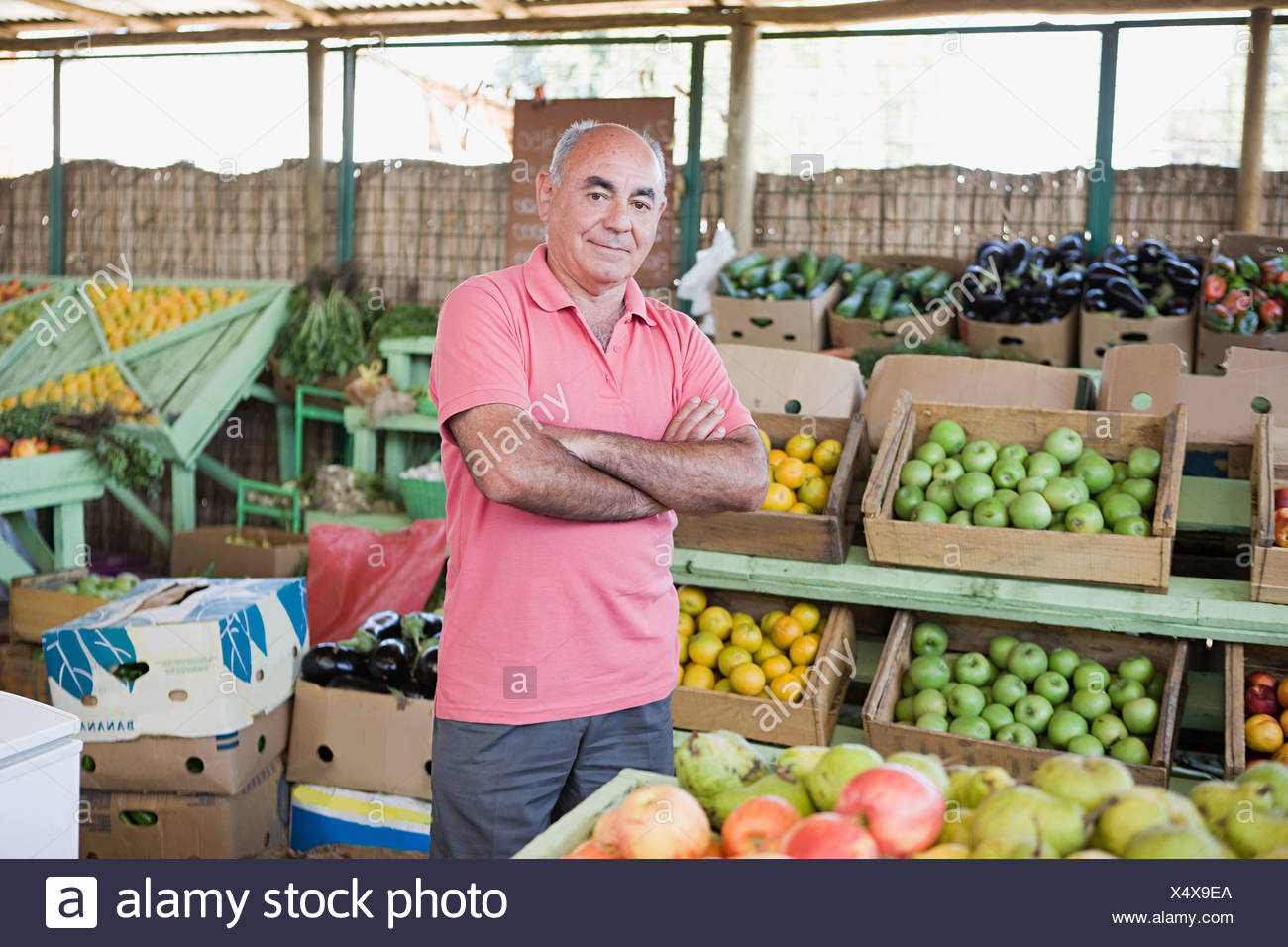Market trader at fruit and vegetable stall - Stock Image