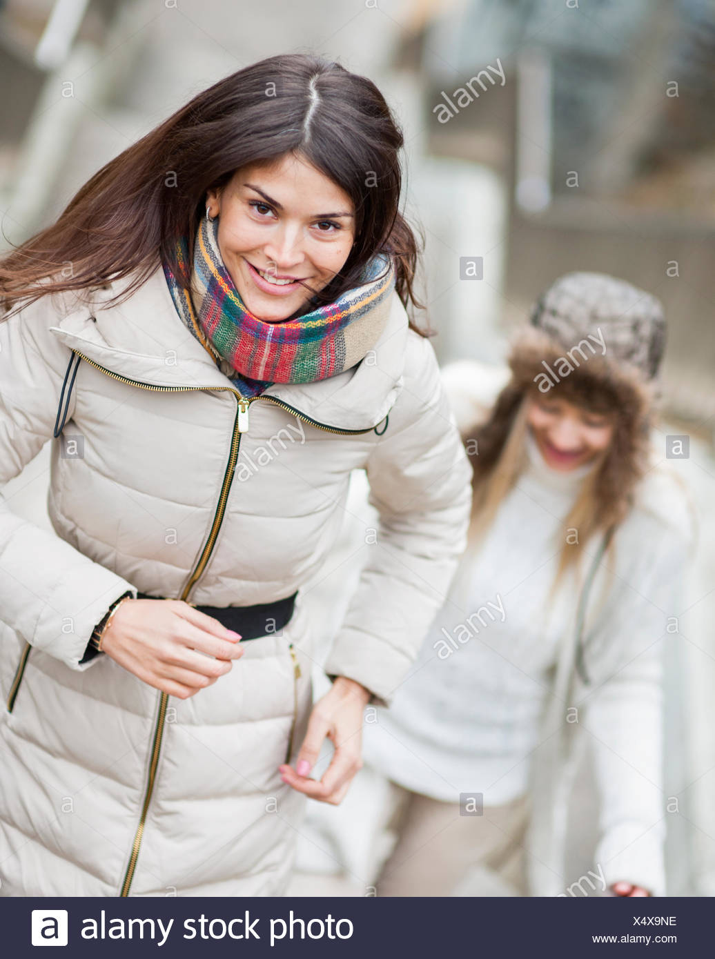 Smiling young woman climbing stairs with friend outdoors - Stock Image
