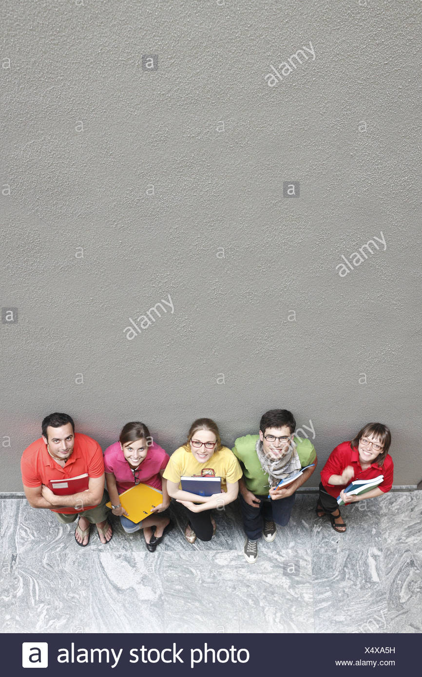 Students leaning against a wall, looking upwards - Stock Image