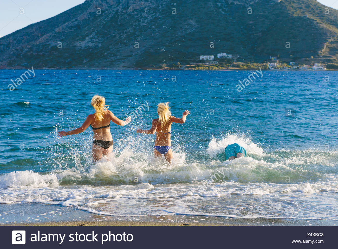 Greece, Dodecanese, Kalymnos, Two women running into sea - Stock Image