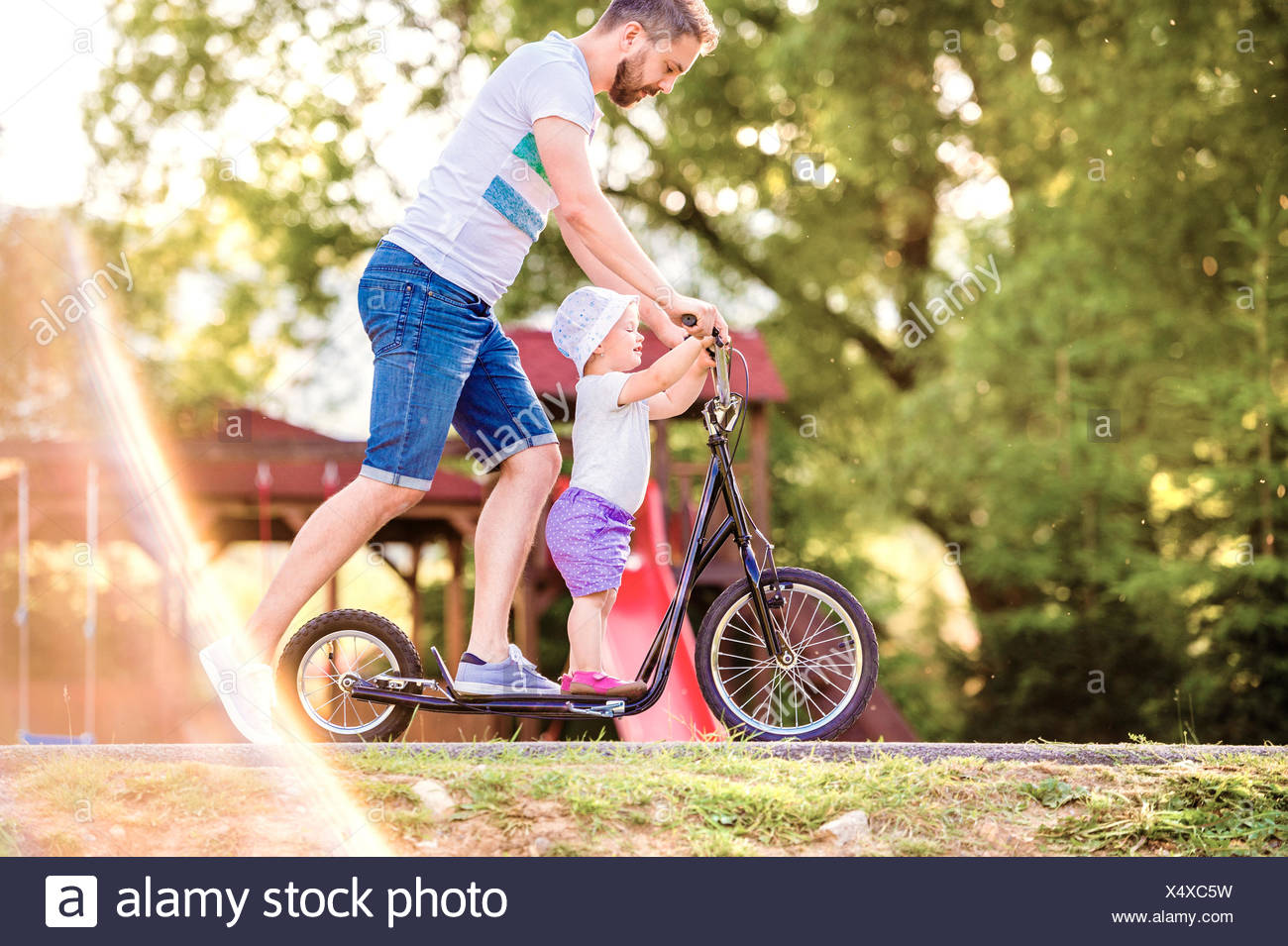 Father and little daughter together on a scooter - Stock Image