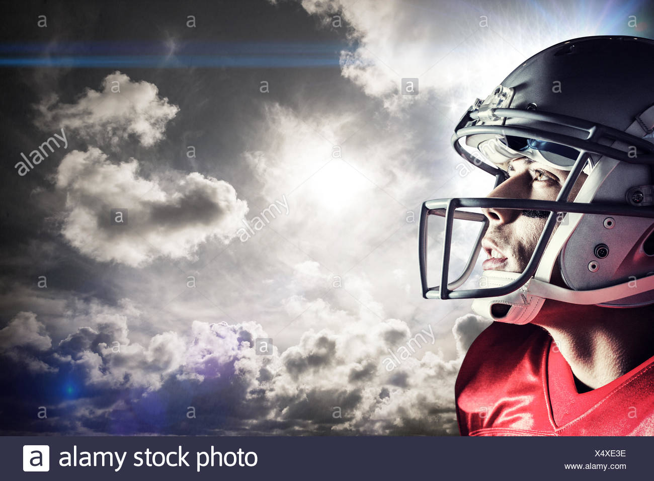 Composite image of american footballer looking up - Stock Image