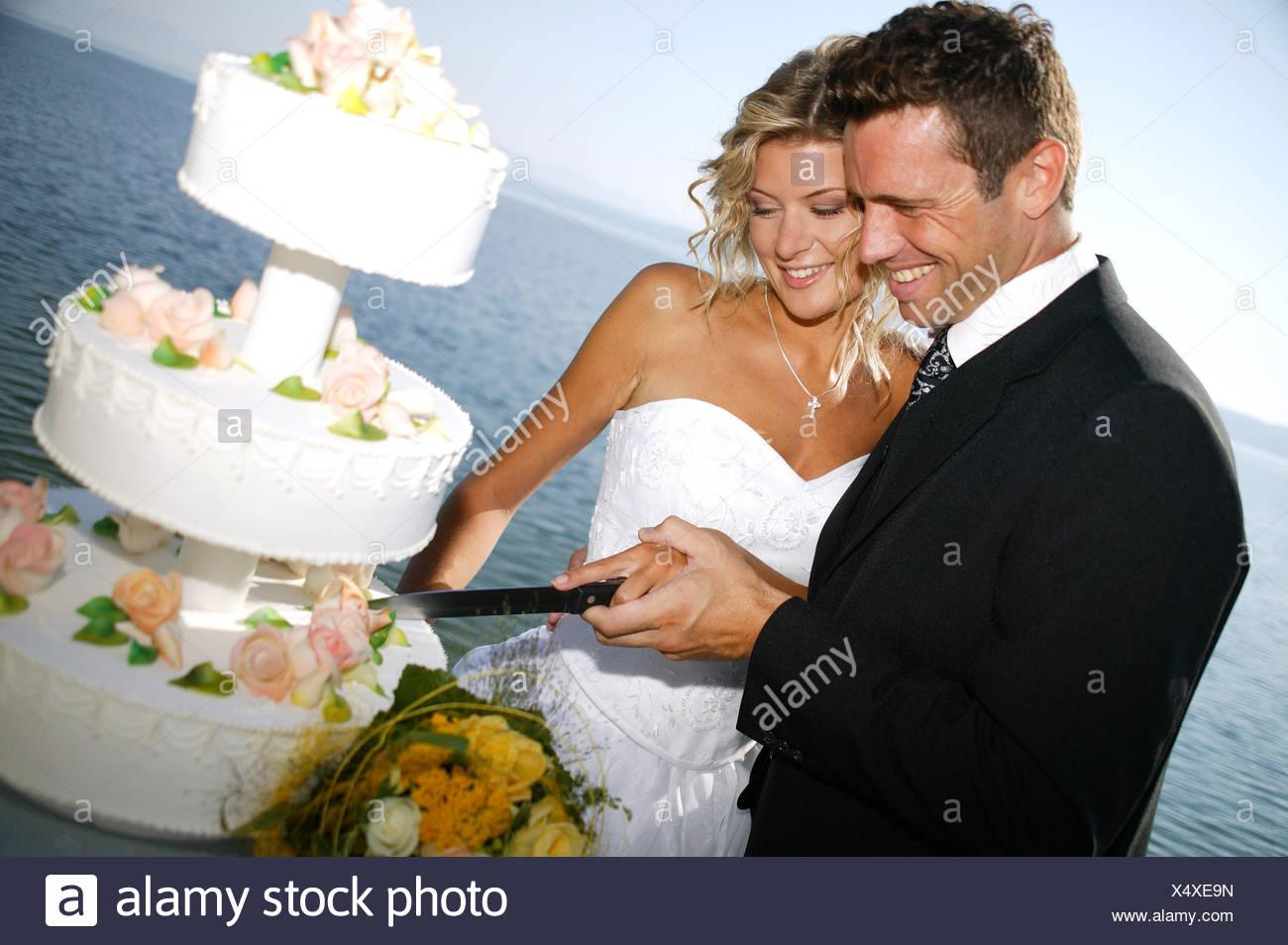 bridal couple outside, with weddingcake Stock Photo