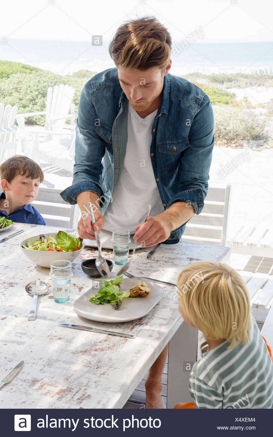 Father serving food to children on table - Stock Image