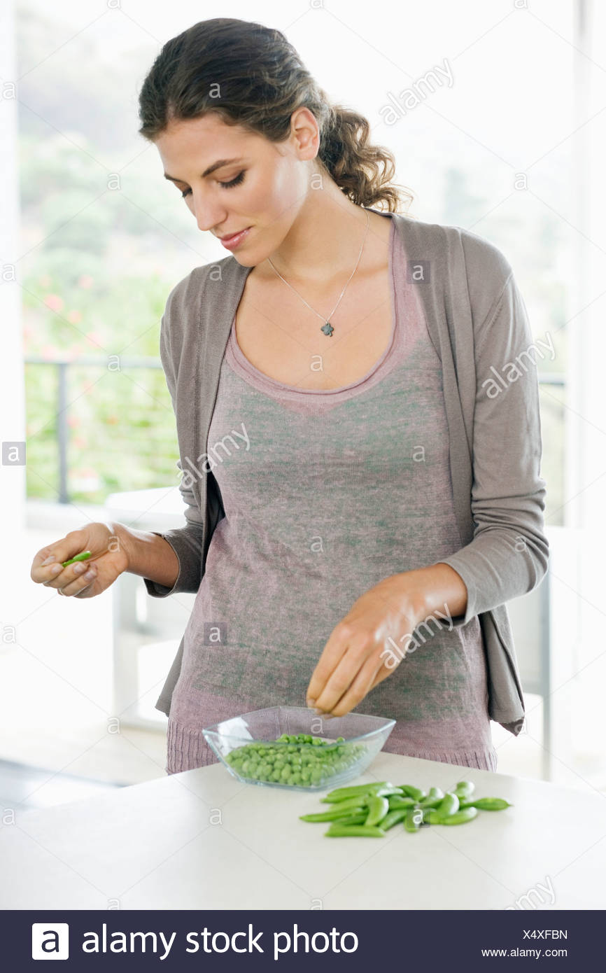 Woman peeling green peas in the kitchen - Stock Image