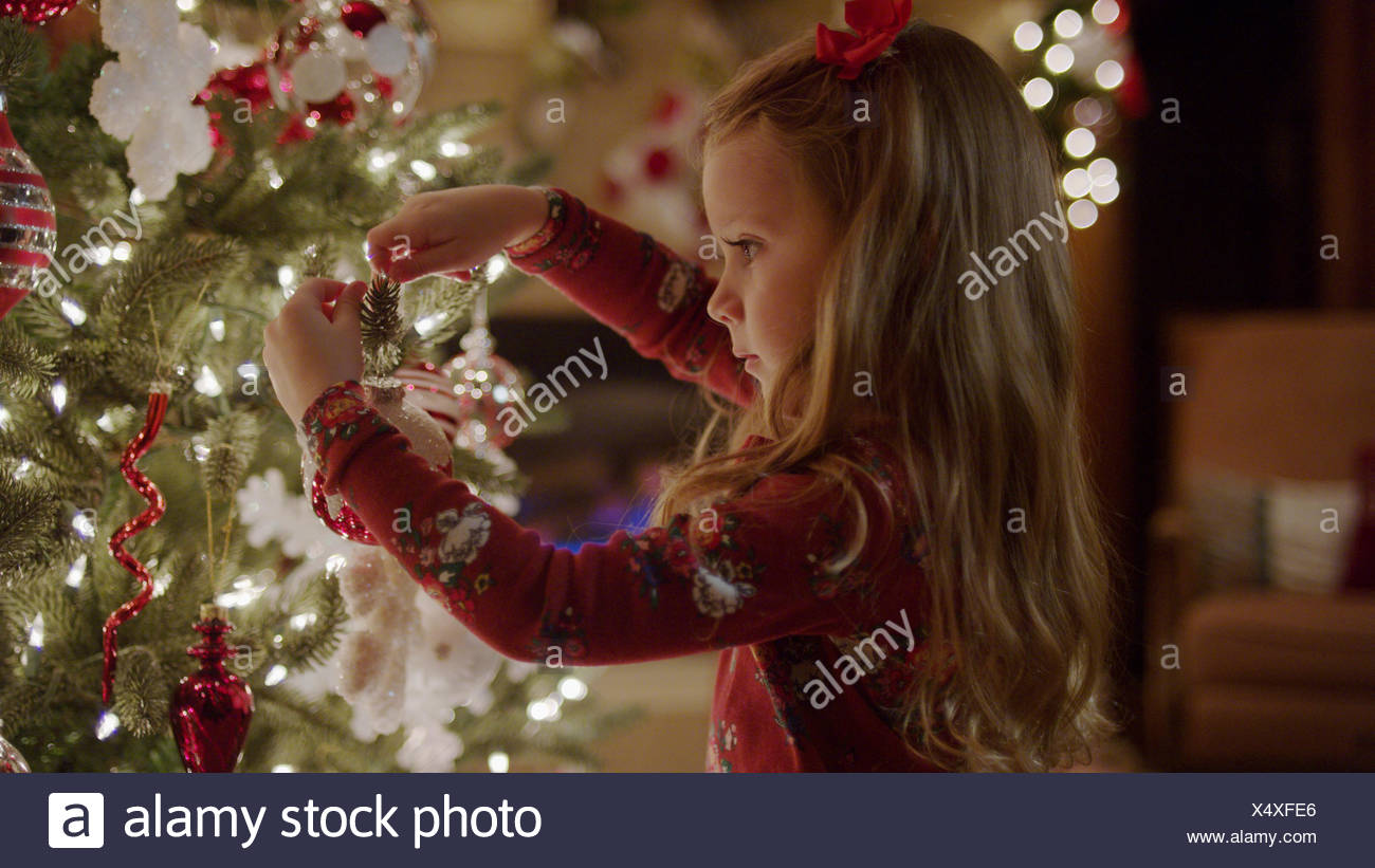 Close up of girl decorating Christmas tree with illuminated lights - Stock Image