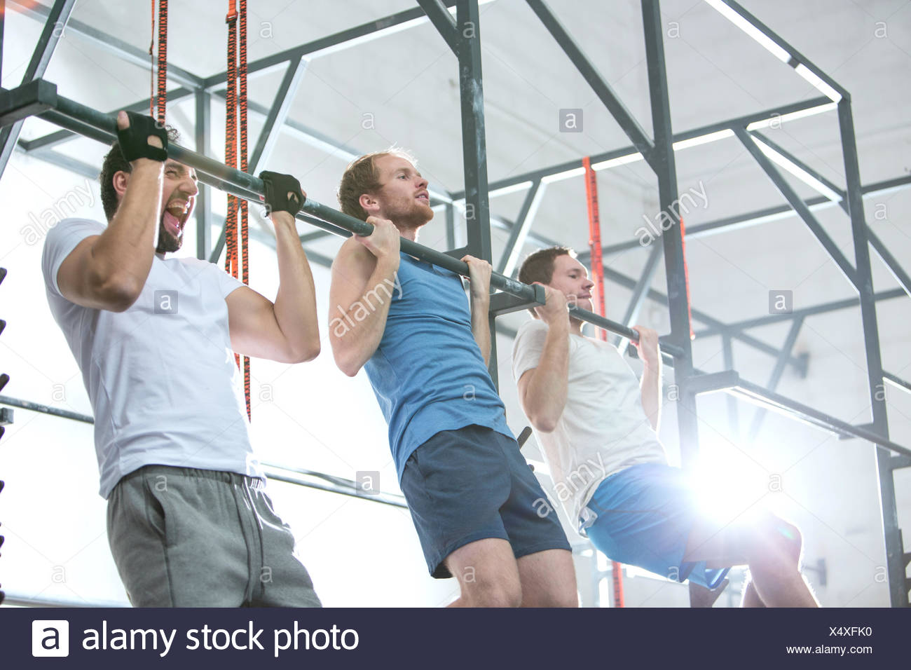 Low angle view of dedicated men doing chin-ups in crossfit gym - Stock Image