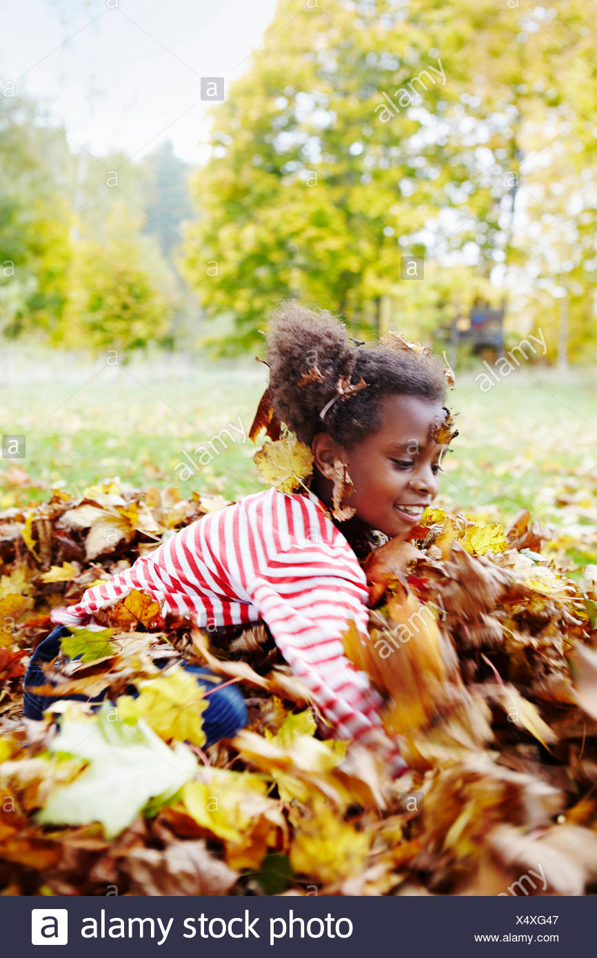 Sweden, Vastra Gotaland, Runnas, Girl (6-7) playing in park in autumn - Stock Image