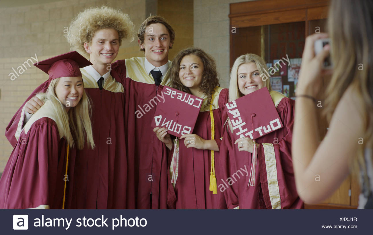 Smiling Students Posing With Decorated Mortarboards At Graduation