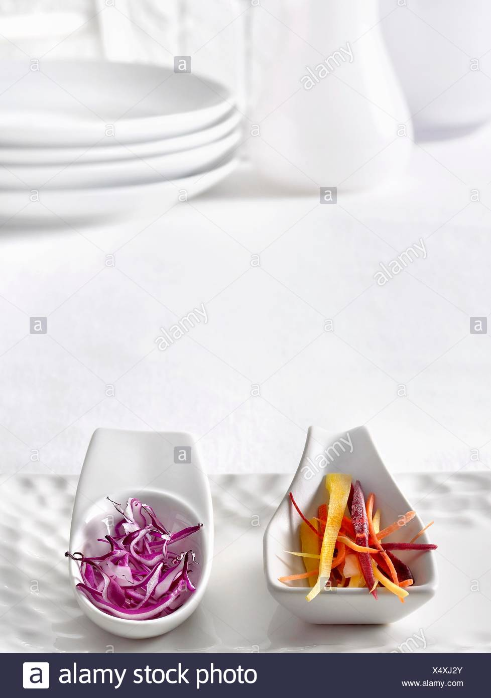 Julienned Organic Multi-Colored Heirloom Carrots and Red Cabbage on White Serving Spoons - Stock Image