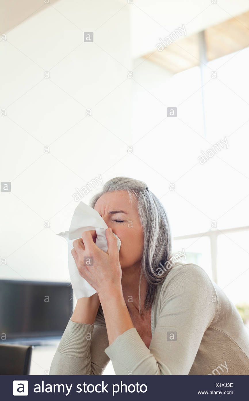 Sick woman blowing her nose - Stock Image