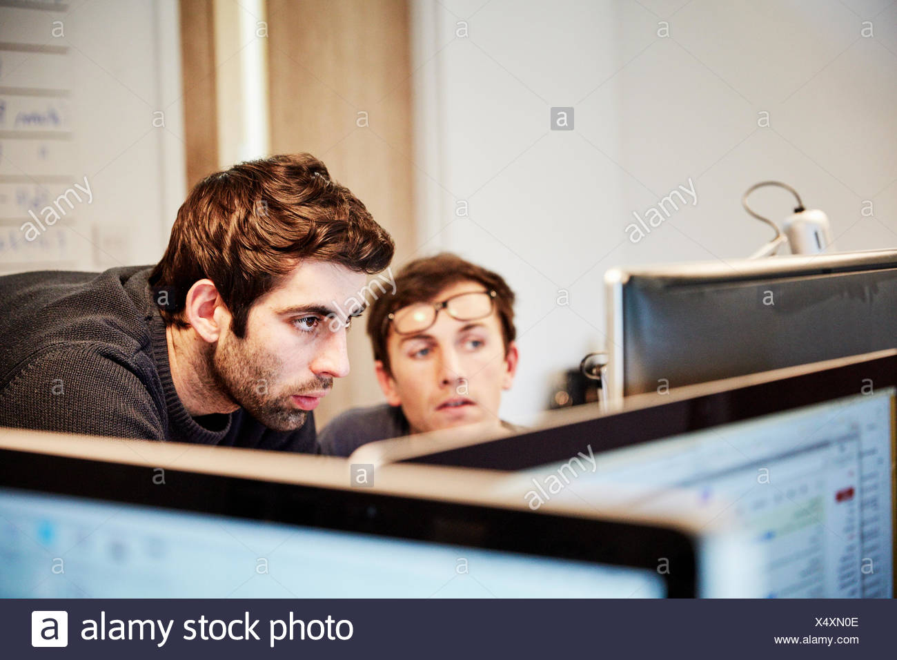 A furniture workshop ,Two people discussing a design referring to drawings and laptop computers - Stock Image