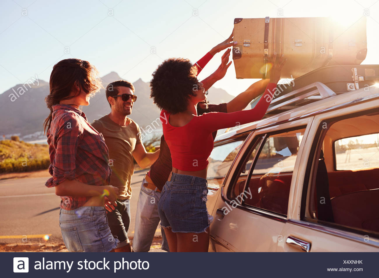 Friends Loading Luggage Onto Car Roof Rack Ready For Road Trip Stock Photo Alamy