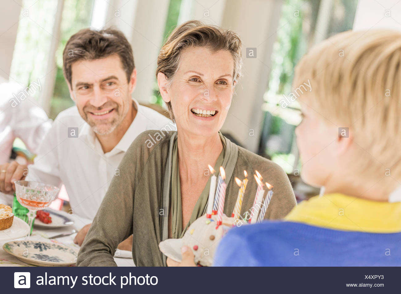Boy handing birthday cake to grandmother at  party - Stock Image