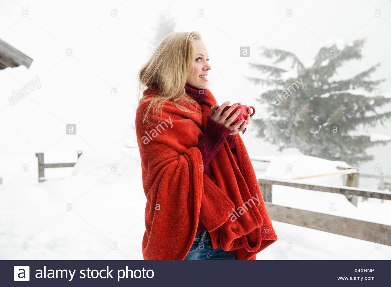Young woman in snowy mist wrapped in red blanket drinking coffee - Stock Image