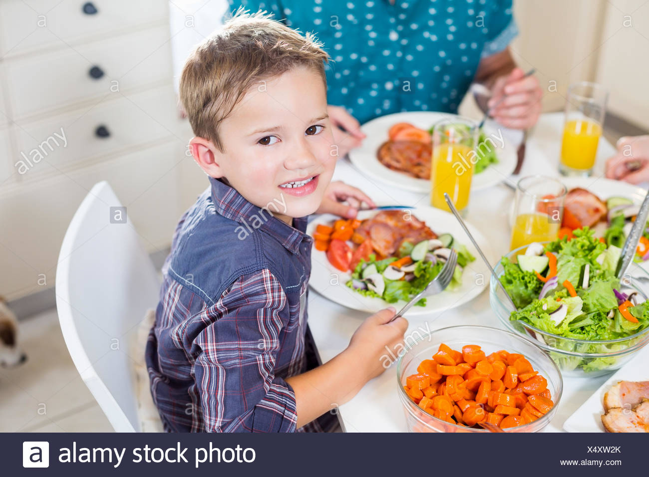 Boy sitting at dining table smiling - Stock Image