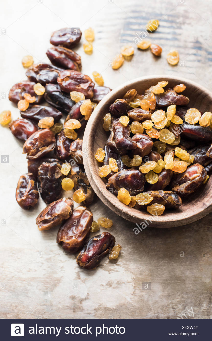 Dried dates and yellow raisins in bowl, close-up - Stock Image