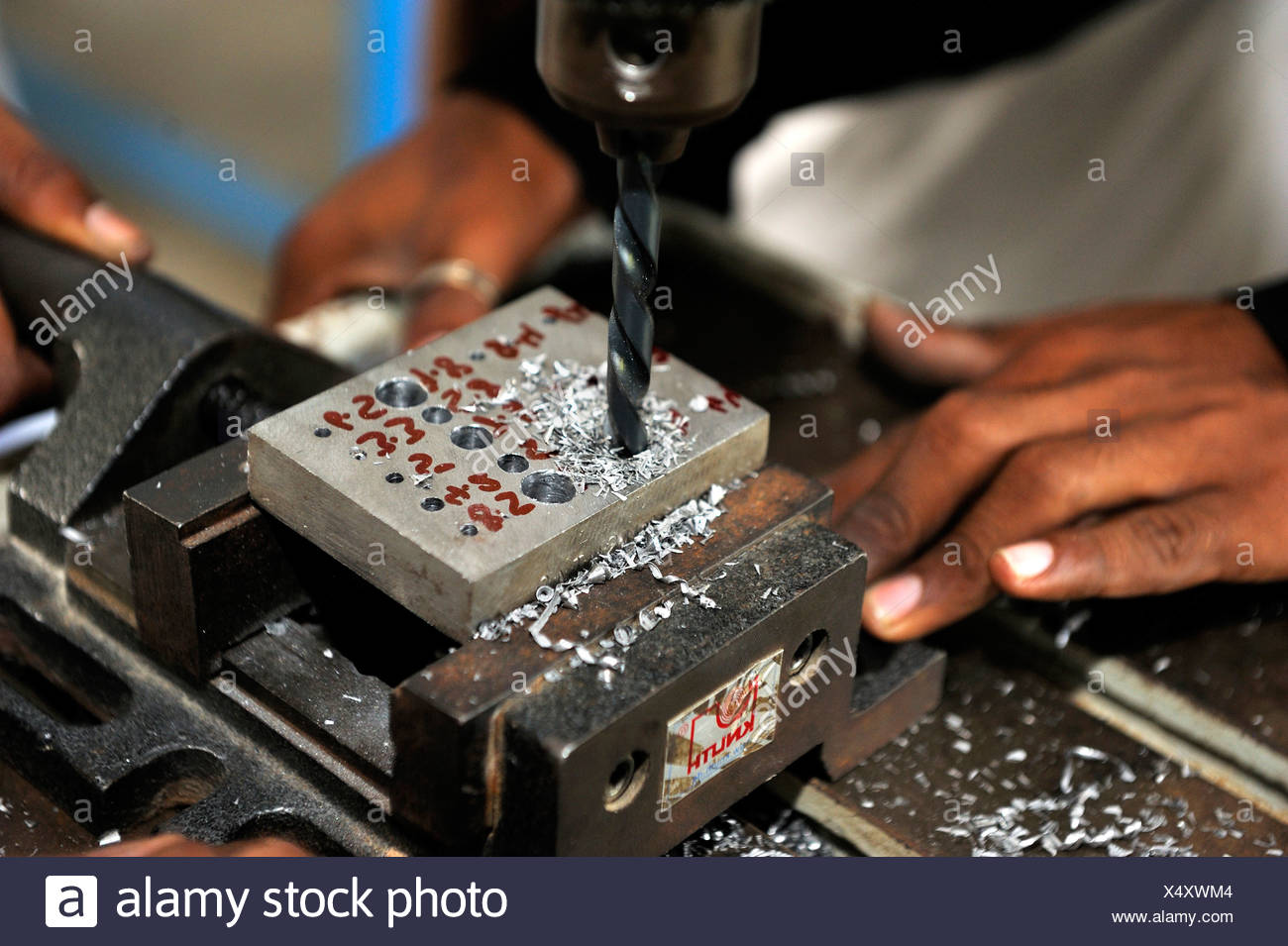 Vocational training as a metalworker, vocational student drilling different size holes in a steel ingot, Youhanabad, Lahore - Stock Image