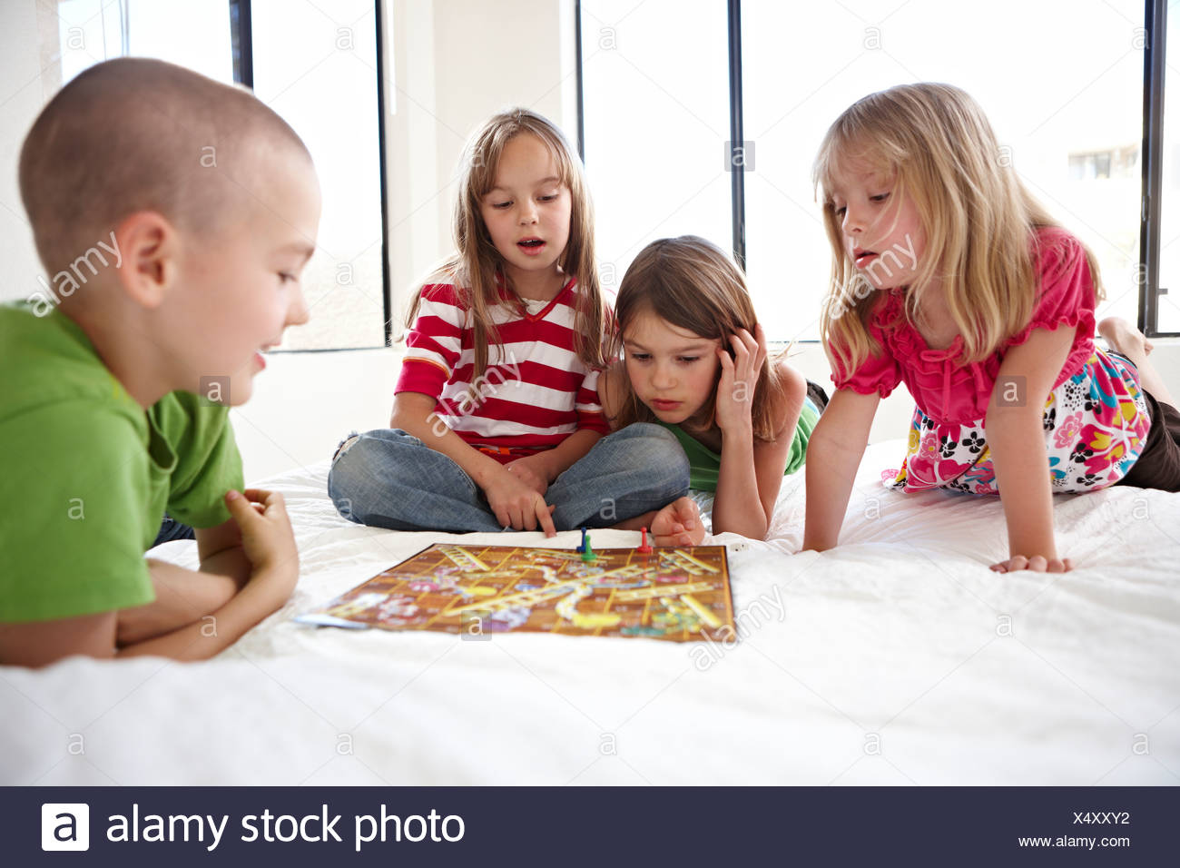 Children playing snakes and ladder on bed stock photo: 278416406.