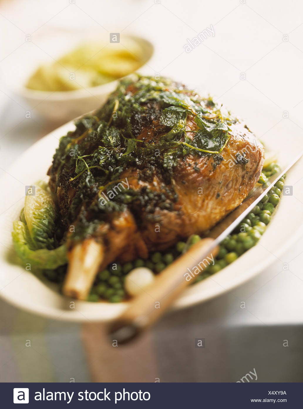 Leg of lamb with herbs, peas and lettuce - Stock Image