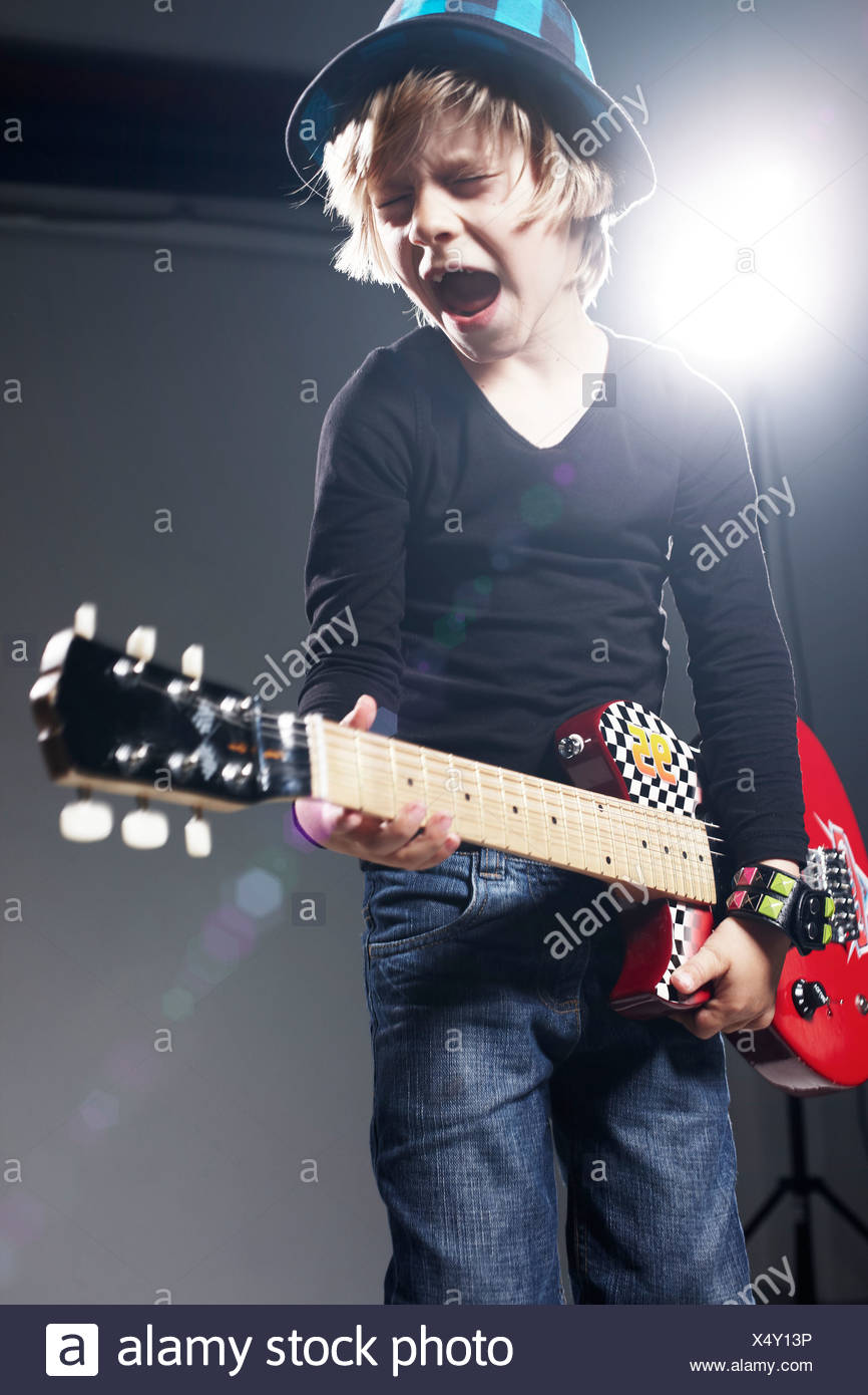 Boy playing paper guitar and singing against grey background - Stock Image