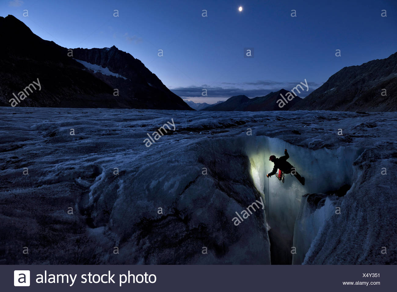 In the early evening light, an Italian cave explorer begins his descent down a moulin on the Aletschgletscher when there is no risk of surface meltwat - Stock Image