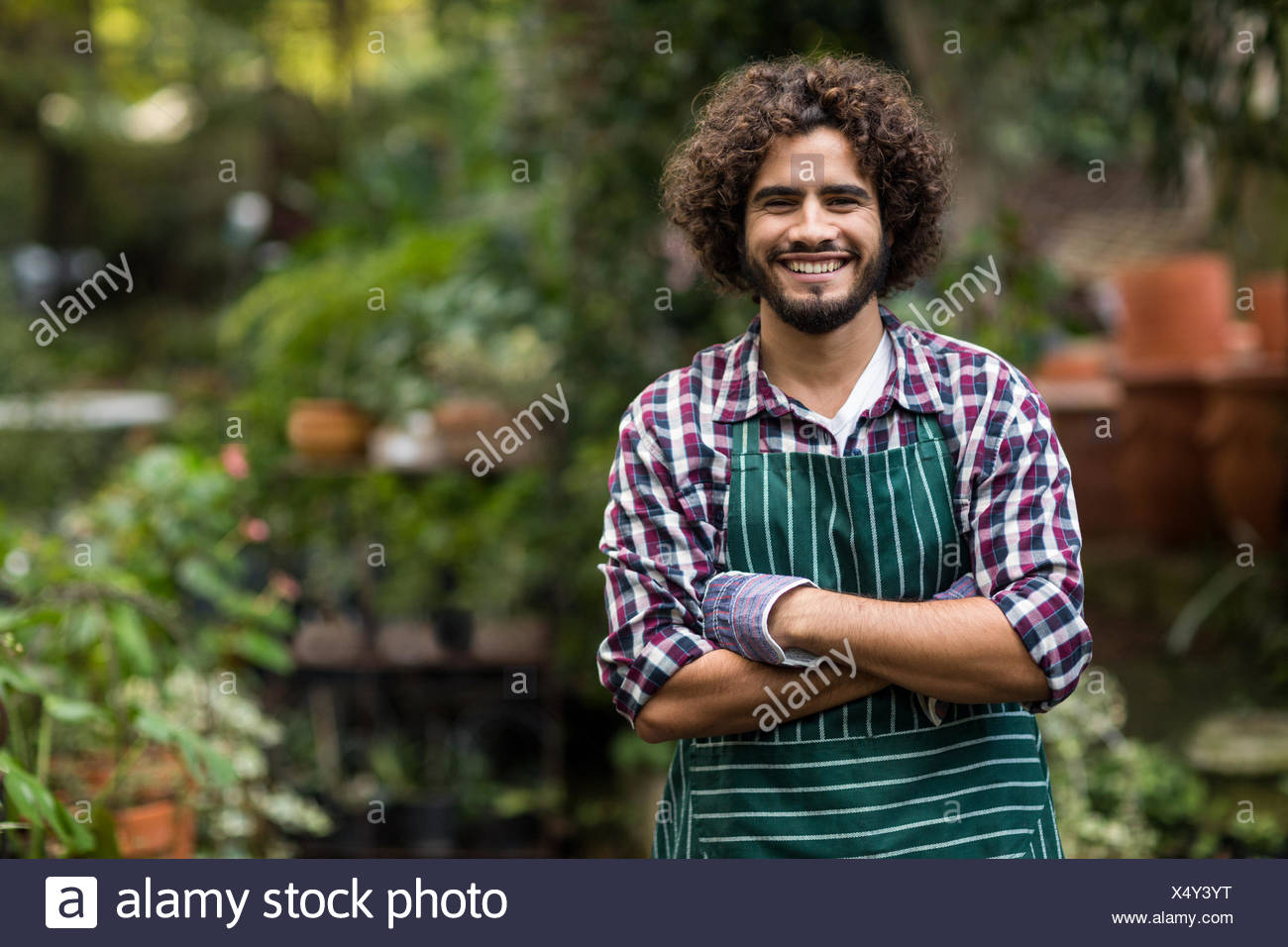 Confident male gardener standing at greenhouse - Stock Image