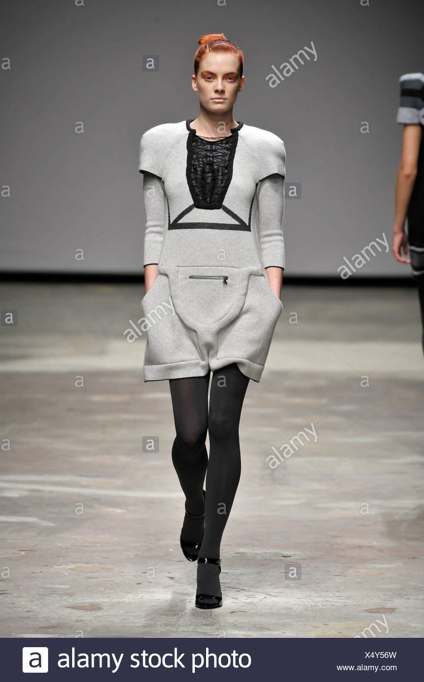 Grey fleece minidress, grey tights and shoes, orange eyeshadow - Stock Image