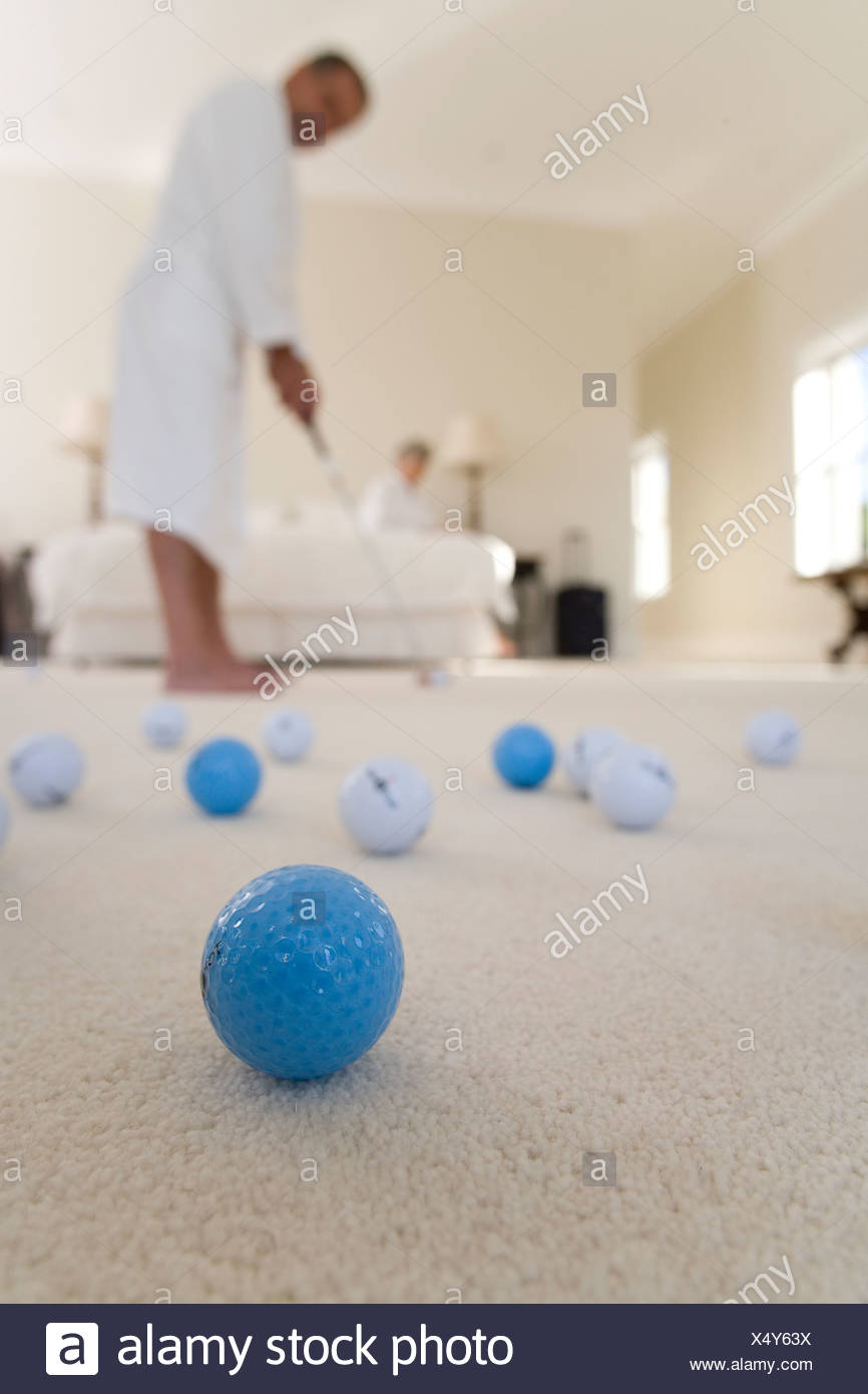 Senior couple in bedroom, man practising golf putt, focus on golf balls in foreground - Stock Image
