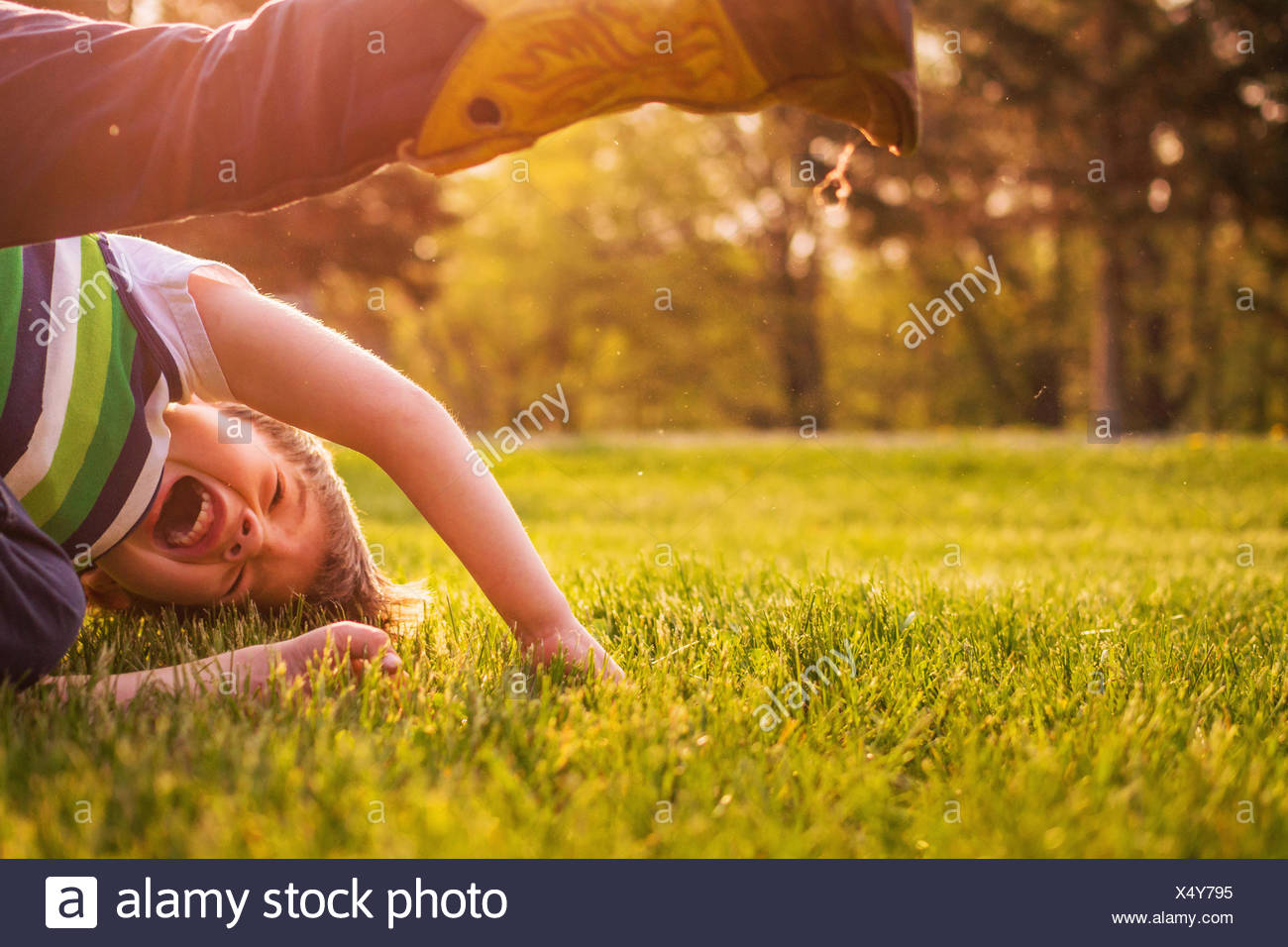 Boy laughing and rolling about on the grass in the garden - Stock Image