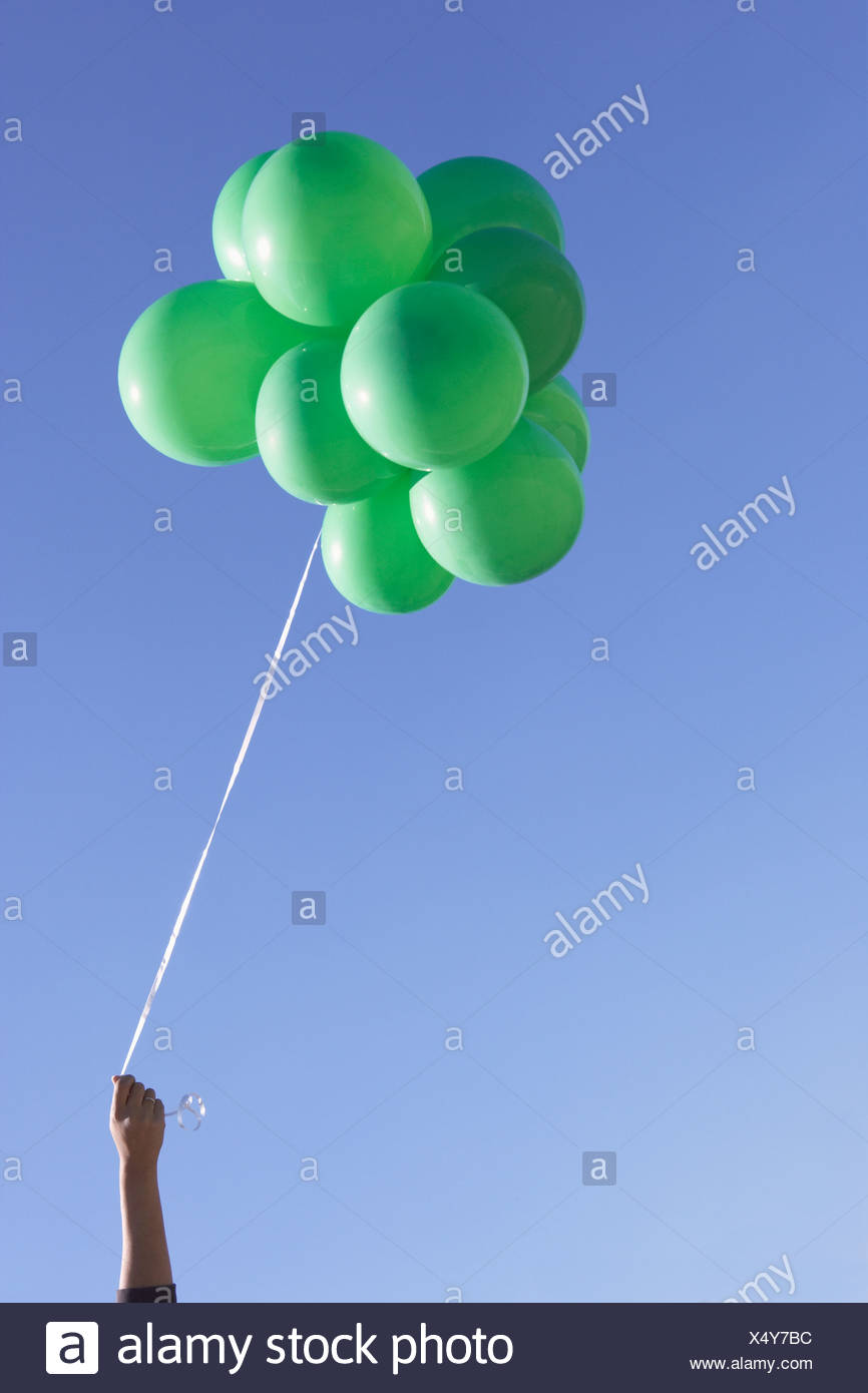 hand holding green balloons - Stock Image