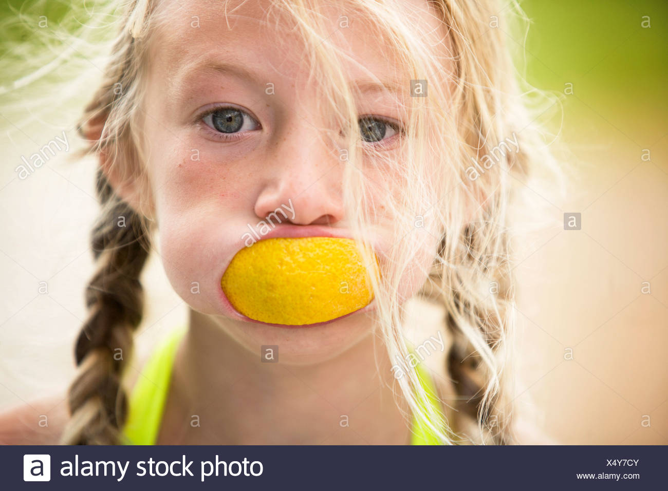 young girl with orange peel in mouth - Stock Image