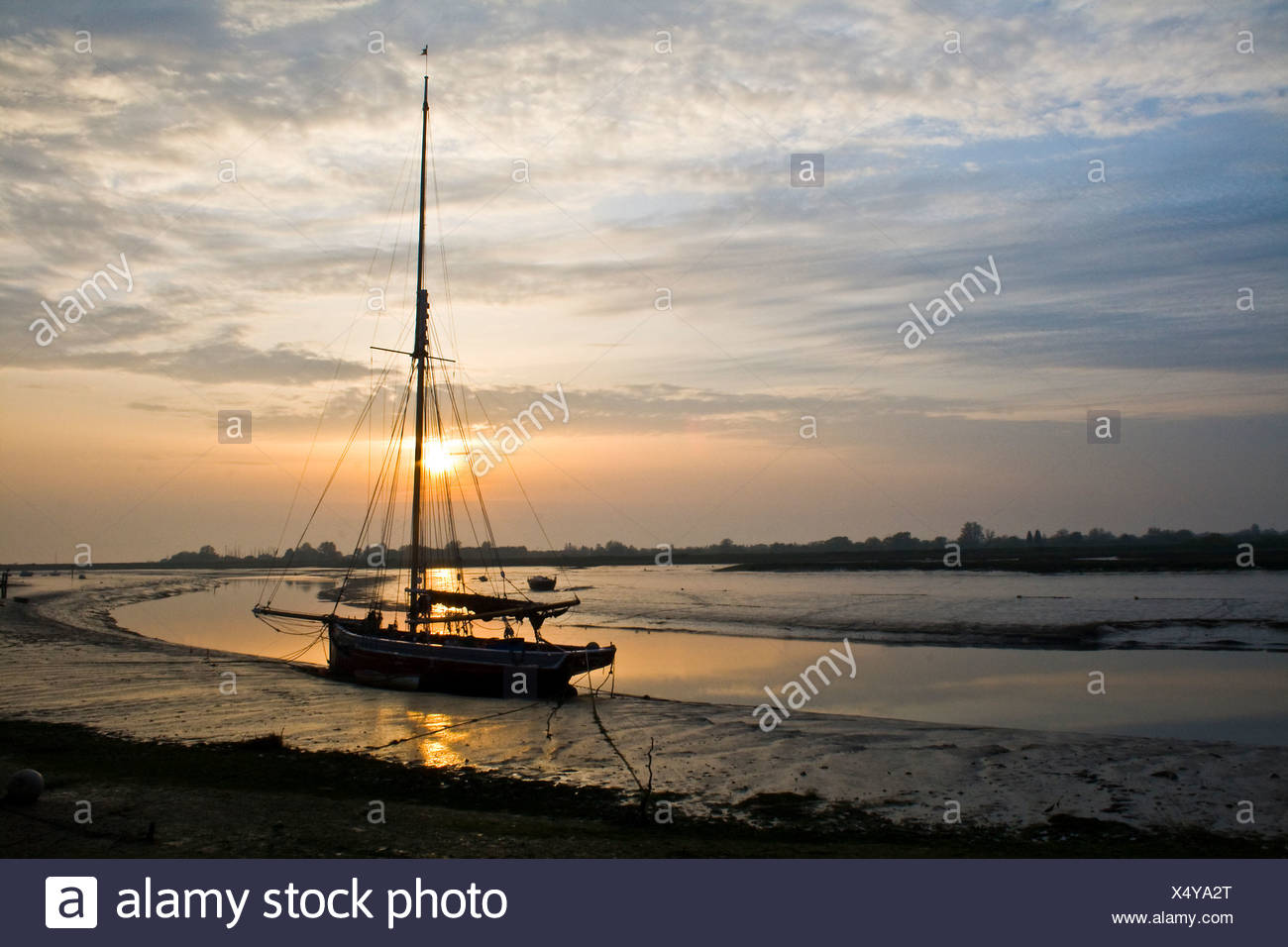 Oyster smack silhouetted against the early morning sun at Maldon, Essex. - Stock Image