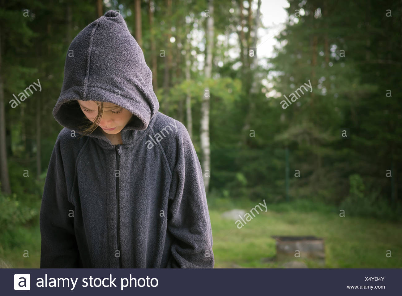 Sweden, Vastergotland, Lerum, Girl in sweatshirt looking at lakeshore - Stock Image