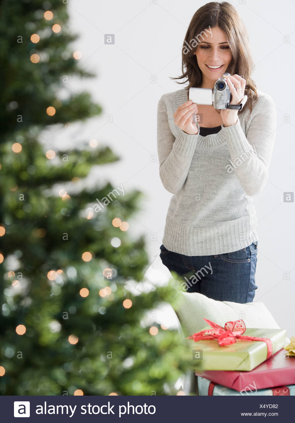 Woman video recording Christmas tree - Stock Image