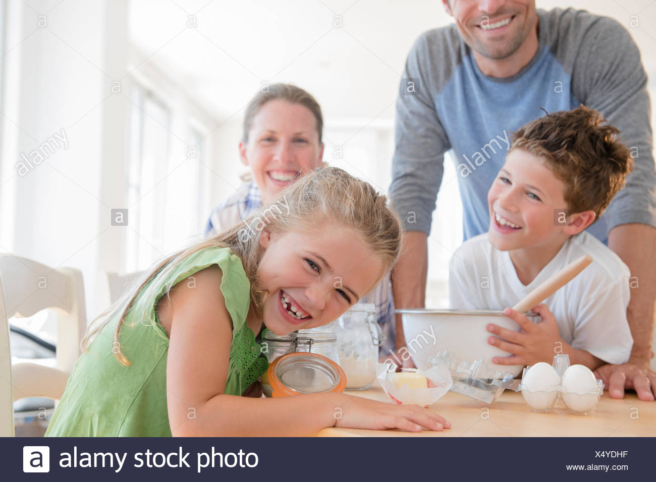 Family with two children (6-7, 8-9) preparing food, laughing - Stock Image