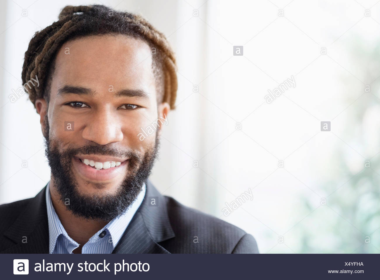 Portrait of smiley businessman wearing suit - Stock Image