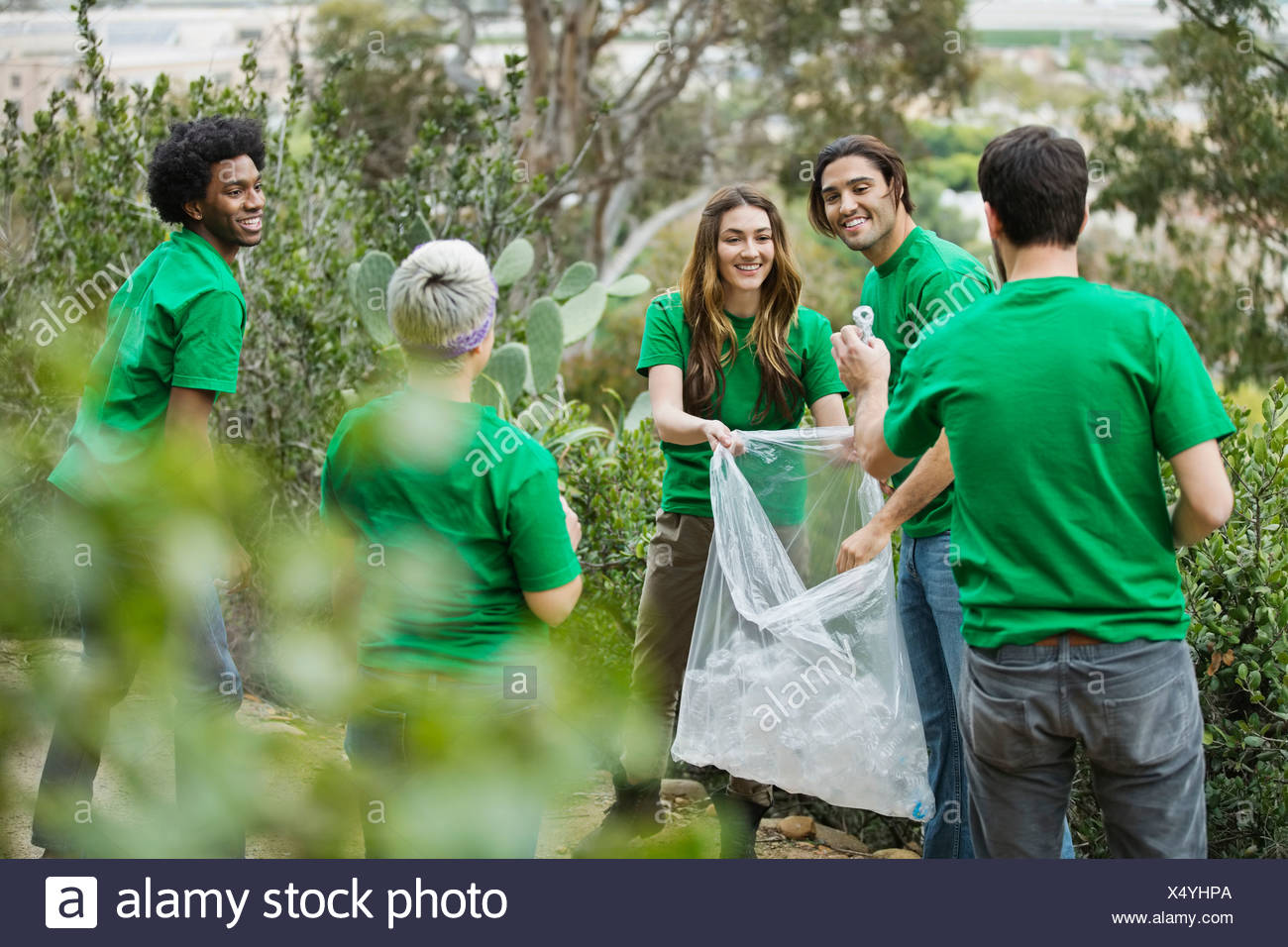 Group of environmentalists collecting empty bottles in plastic bag at park - Stock Image
