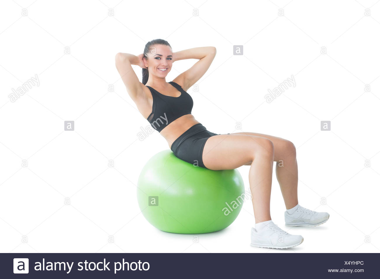 Gorgeous active woman practicing an exercise on an exercise ball - Stock Image