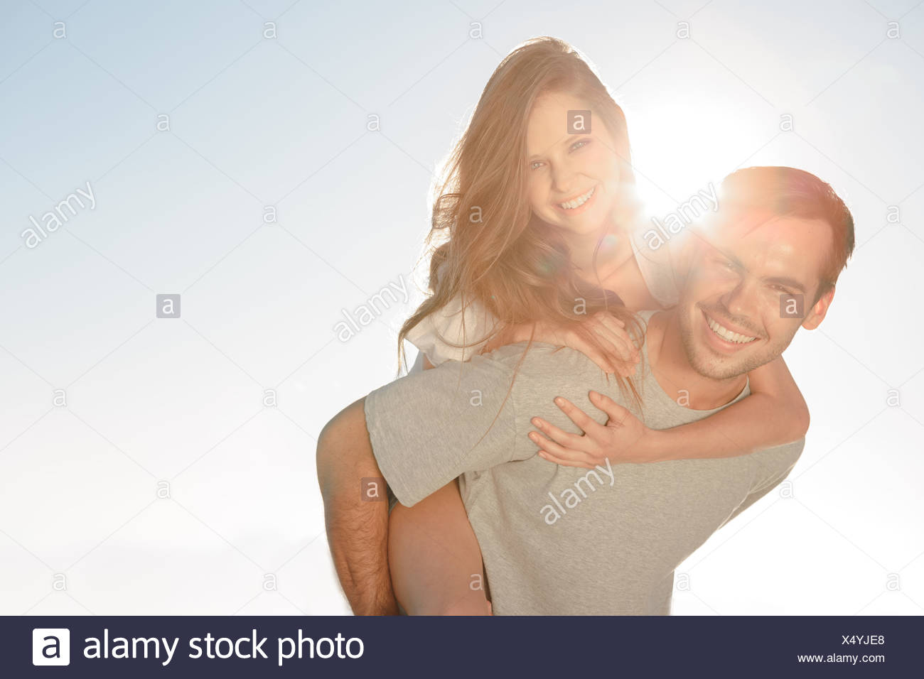 Happy man giving a piggy back to his girlfriend - Stock Image