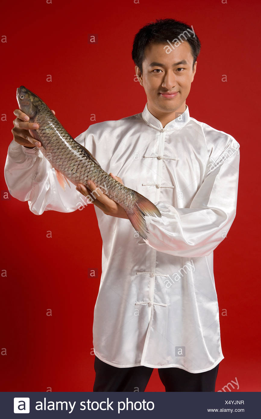 Man Showing Off Raw Fish - Stock Image