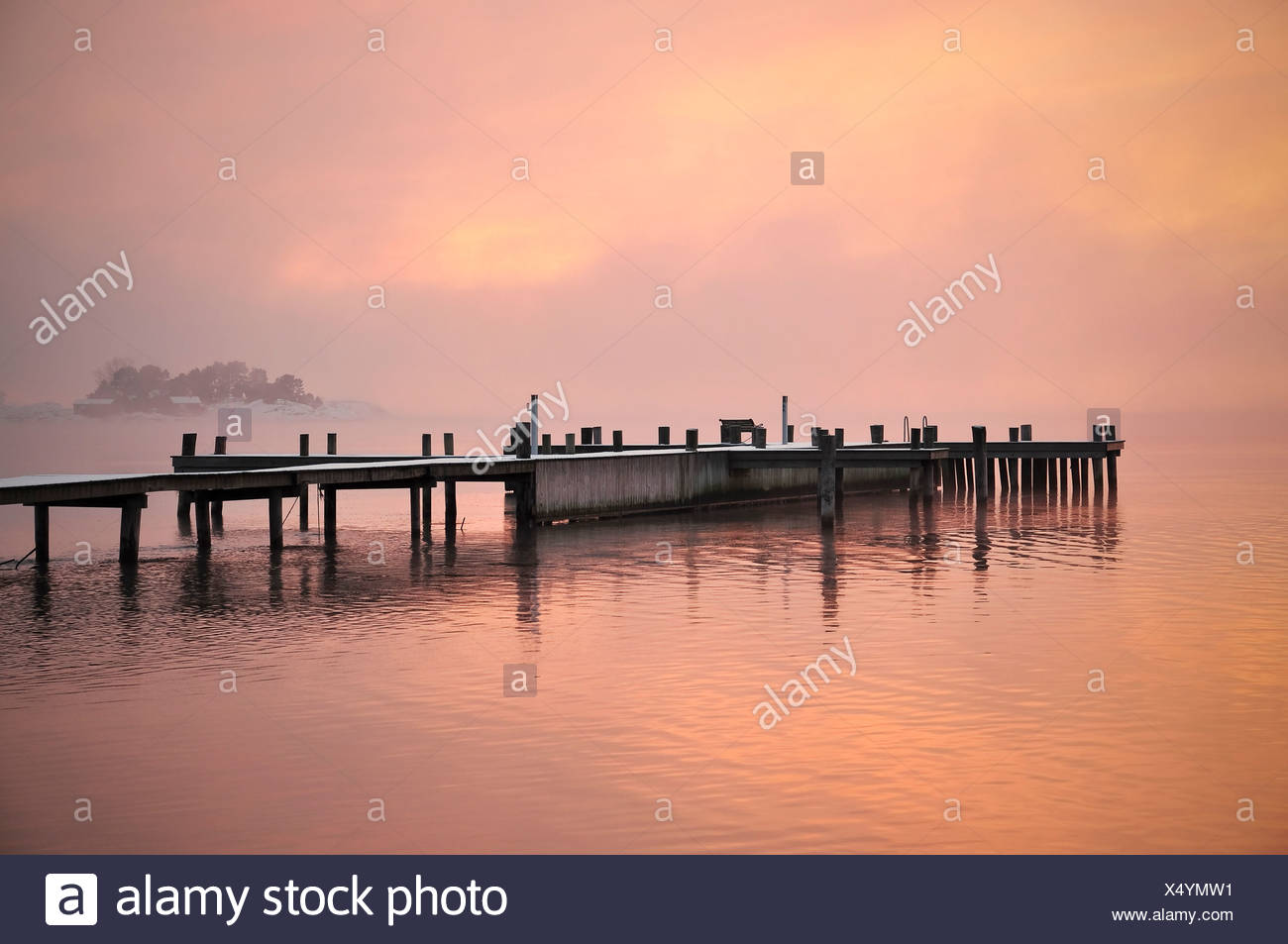 Jetty surrounded by water at dusk - Stock Image
