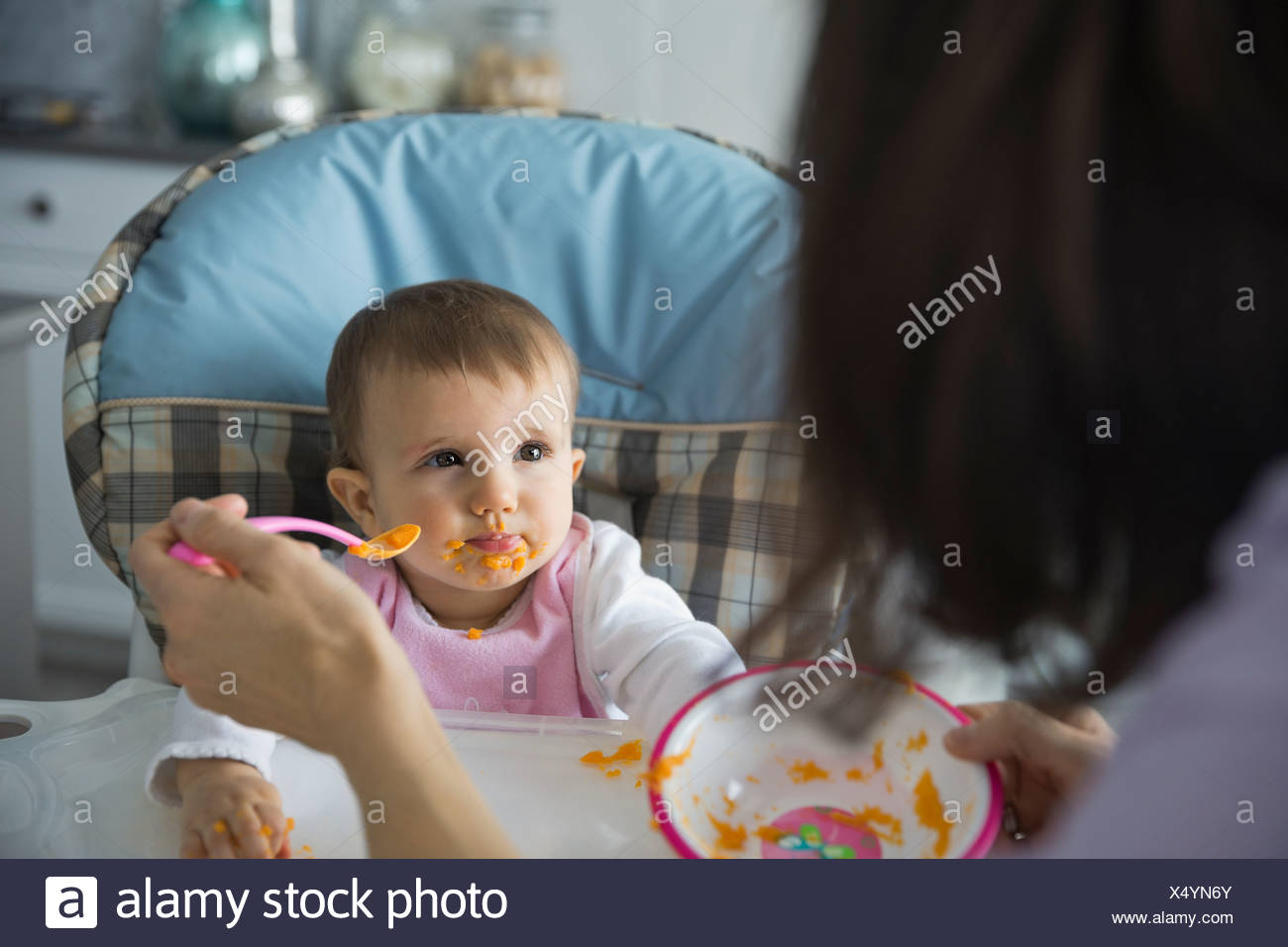 Cute baby girl being fed by mother at home - Stock Image