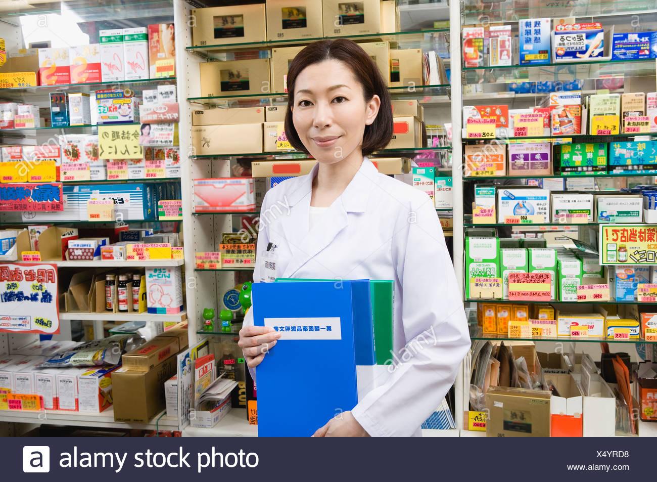 Pharmacist Holding File of Description for Type-1 OTC Drugs - Stock Image